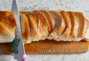 нарезать батон для приготовления бутербродов со шпротами и солеными огурцами