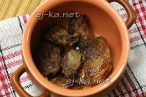 Обжаренную свинину переложите в горшочки