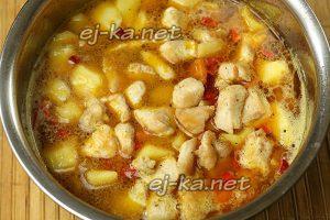 Влить воду в кастрюлю с рагу из овощей и курицы