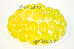 Прикрепляем на слой майонеза половинки виноградин по всей поверхности салата