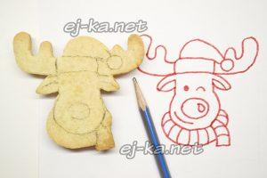 На готовом печенье рисуем контуры шарфика, шапки и мордочку весёлого оленя