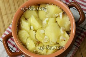 Посыпьте картошку чесноком, закройте крышечкой горшочек и ставьте в горячую духовку