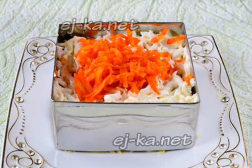 натереть яичные белки и выложить поверх консерв, затем тертую морковь