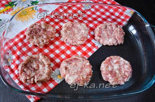 сформировать из мясного фарша лепешки и выложить их на противень либо в форму для запекания, которую необходимо слегка смазать растительным маслом