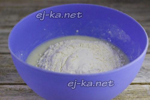 после просеем пшеничную муку через мелкое сито и небольшими порциями насыпаем в кефирно-яичную массу