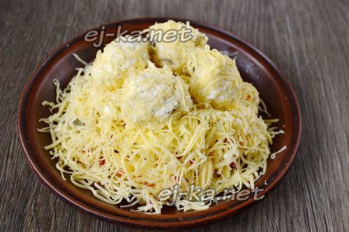 уложить шарики поверх салата и посыпать тертым сыром